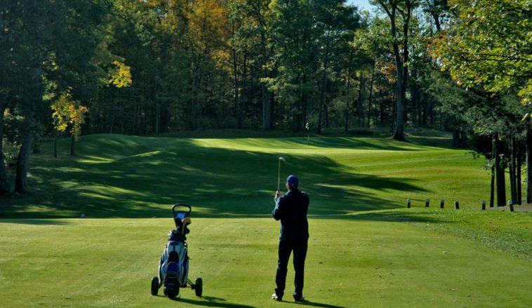 Man watching golf shot