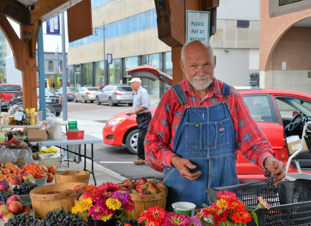 A vendor at the Farmers Market selling fruits and flowers